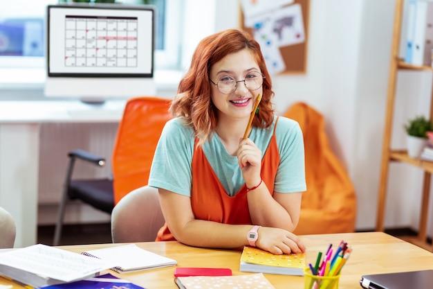 I miei compiti. donna dai capelli rossi contentissima che sorride mentre tiene la sua matita