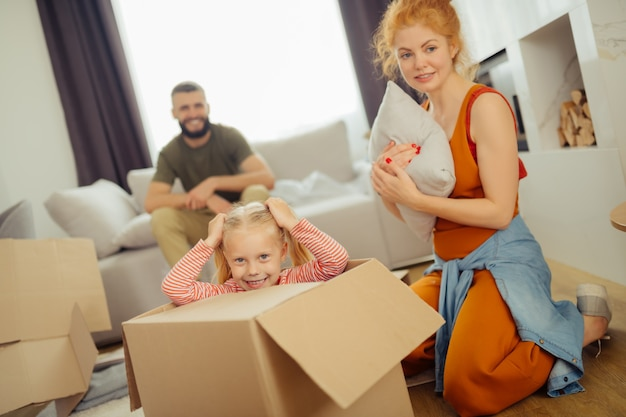 La mia casa. allegra ragazza positiva seduta nella scatola mentre finge che sia la sua casa