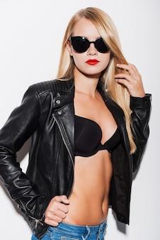 La mia vita le mie regole. fiduciosa giovane donna in reggiseno nero e giacca di pelle che si tocca i capelli