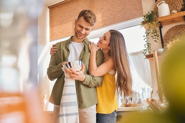 Il mio amore. positiva coppia felice di essere in cucina e pulire le ciotole dopo aver fatto colazione