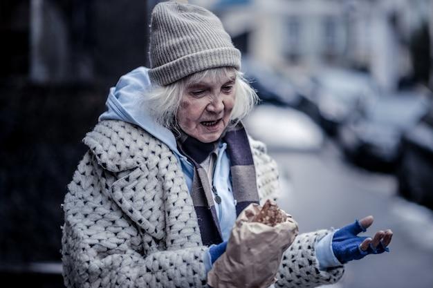 Il mio pranzo. cupa povera donna che tiene un sacchetto con la pasticceria pur avendo qualcosa da mangiare