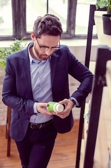 La mia medicina. bell'uomo intelligente in piedi con una bottiglia mentre legge un'iscrizione su di esso