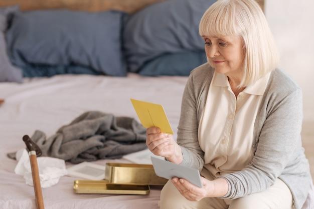 I miei ricordi. triste triste donna senior guardando la vecchia cartolina e sensazione di nostalgia mentre gira le vecchie lettere