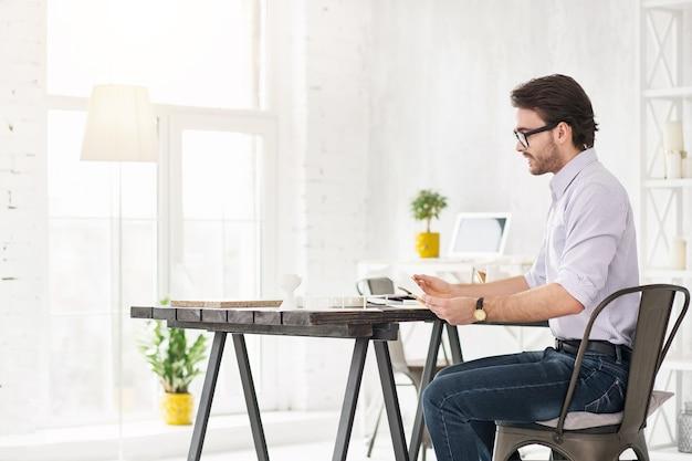 Il mio lavoro. uomo barbuto serio che si siede al tavolo e che tiene alcuni fogli di carta