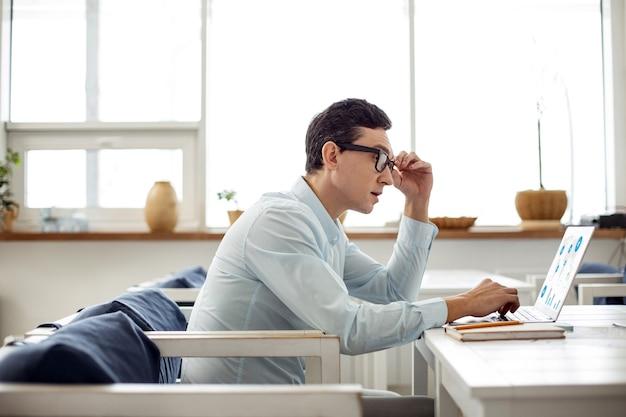 Il mio progetto. bell'uomo dai capelli scuri serio che lavora al suo laptop e tocca gli occhiali mentre era seduto al tavolo
