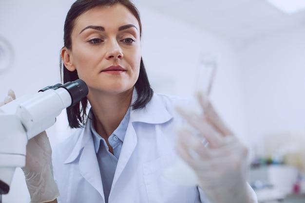 Il mio progetto. scienziato esperto ispirato che lavora con un microscopio e tiene in mano un tubo