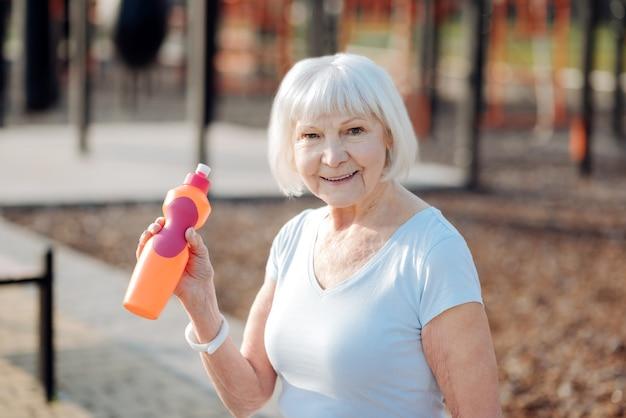 La mia ricreazione. felice donna bionda bere succo di frutta e rilassarsi durante l'allenamento