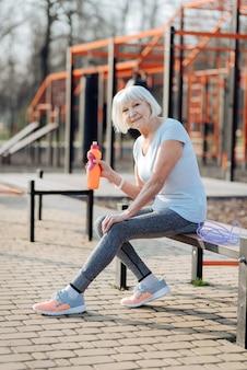 Il mio riposo. felice donna sottile in possesso di una bottiglia di succo di frutta e rilassarsi durante l'allenamento