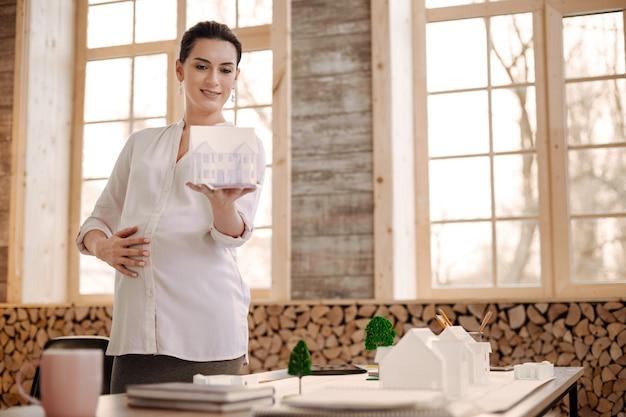 Il mio lavoro. affascinante designer incinta attraente che trasporta il modello della casa mentre sorride e mette la mano sulla pancia