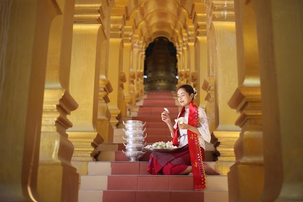 Donne del myanmar che tengono i fiori in un tempio. ragazze del sud-est asiatico con abiti tradizionali birmani in visita a un tempio buddista