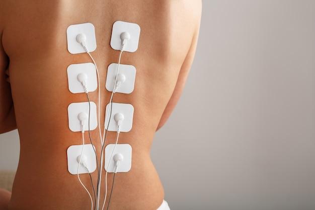 Elettrodi per miostimolazione sulla schiena di una donna per massaggio e riabilitazione. trattamento, perdita di peso.