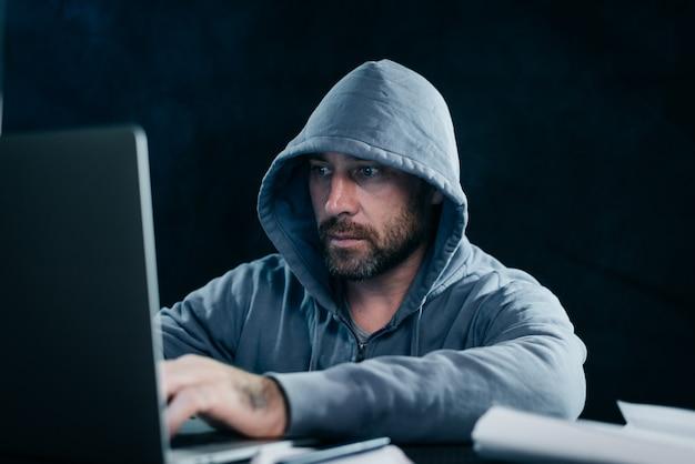 Misterioso uomo barbuto hackera un laptop, in un cappuccio, al buio