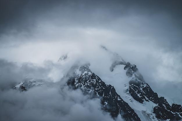 Misterioso scenario alpino drammatico con montagne innevate