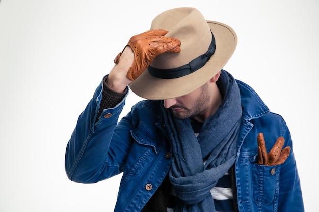 Misterioso uomo di moda in giacca di jeans, sciarpa, cappello e guanti di pelle marrone in posa su un muro bianco