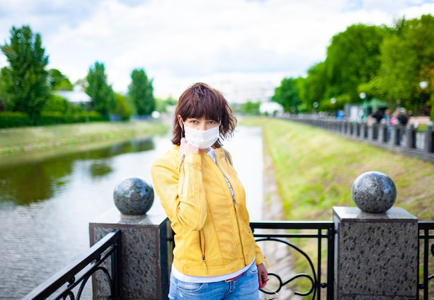 Misteriosa donna non identificata pensierosa cammina nel parco in una maschera protettiva