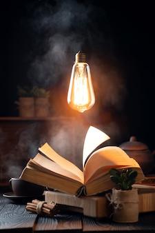 Composizione mistica con un libro magico, vapore da un libro e una lampadina sospesa nell'aria
