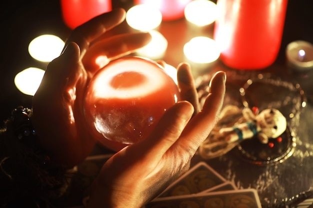 Natura morta mistica con bambola voodoo le carte dei tarocchi libri candele malvagie e oggetti di stregoneria