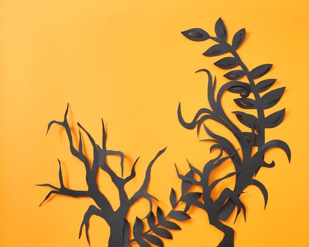 Modello mistico di foglie artigianali di carta nera e rami di alberi su uno sfondo arancione con spazio per il testo. layout di halloween. lay piatto