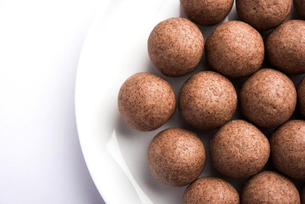 Nachni laddu o ragi laddoo o palline fatte con miglio, zucchero e burro chiarificato. è un alimento salutare dall'india. servito in una ciotola o piatto con crudo intero e polvere. messa a fuoco selettiva