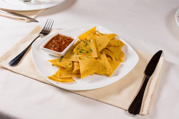 Nacho chips e salsa sul piatto al coperto nel ristorante