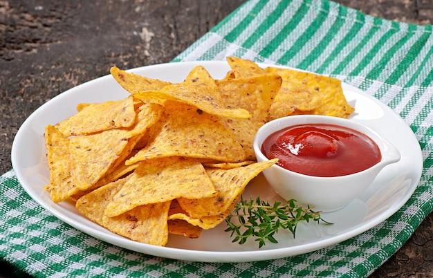 Nachos e salsa di pomodoro decorati con foglie di timo