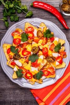 Nachos con salsa di formaggio fuso, jalapeno, pollo e verdure.