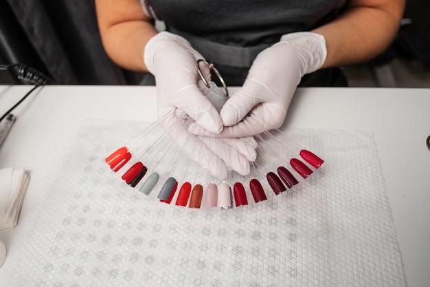 Tavolozza dei colori delle unghie nella donna mani vista dall'alto desktop manicure