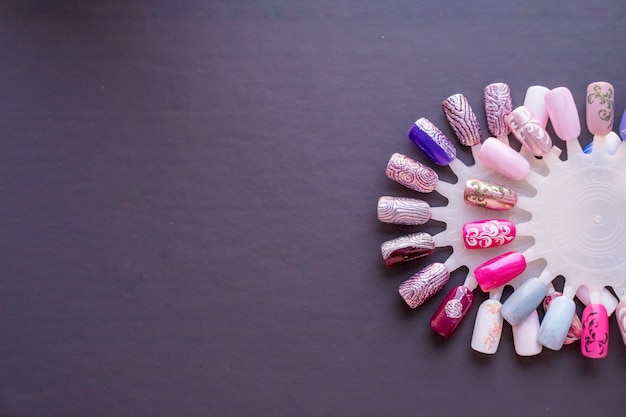 Campioni di colori per unghie in diversi colori. collezione di unghie artificiali dipinte in diversi dispositivi di raffreddamento. campioni di manicure.