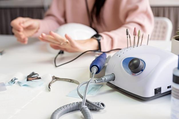 Trapano per unghie o macchina per manicure sul tavolo nel salone di bellezza