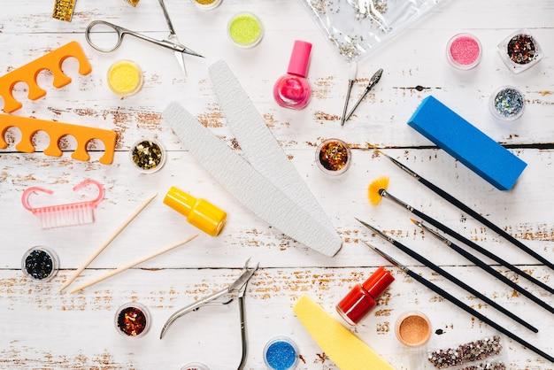 Lima per unghie, forbici, pinze, paillettes e smalti per unghie su un tavolo di legno bianco.