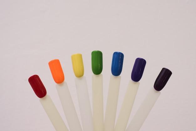 Campioni colorati di smalto nei colori dell'arcobaleno. set di unghie artificiali. vista dall'alto, copia spazio per il testo