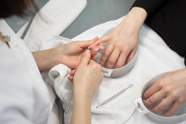 Salone per le unghie. primo piano della mano femminile con unghie naturali sane ottenendo la procedura di cura delle unghie. mani che rimuovono le cuticole con strumento professionale per unghie, tagliaunghie in metallo. manicure di bellezza