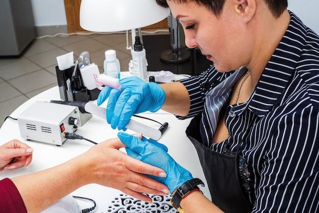 Salone per unghie, mani del cliente e primo piano del maestro. trattamento unghie con lima per manicure