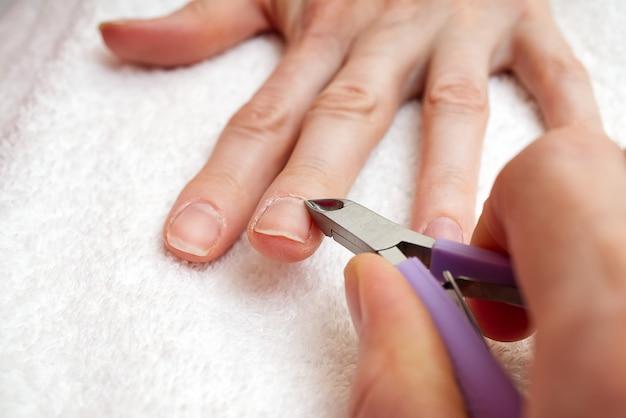 Salone per le unghie. processo di manicure nel salone di bellezza oa casa. primo piano della mano femminile con i chiodi naturali sani che ottengono procedura di cura dell'unghia. mani del primo piano che rimuovono le cuticole con lo strumento professionale del chiodo.