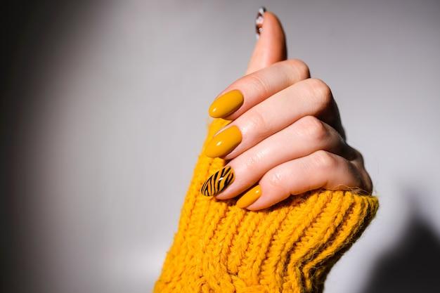 Design delle unghie. mani con il manicure giallo brillante sullo sfondo. primo piano di mani femminili. nail art. manicure della tigre
