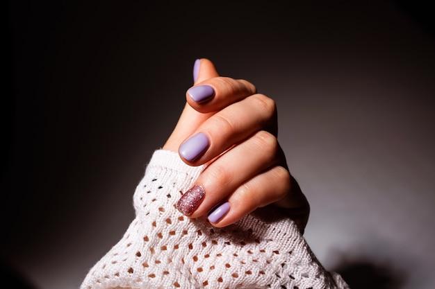Design delle unghie. mani con manicure estivo di colore lilla su grigio