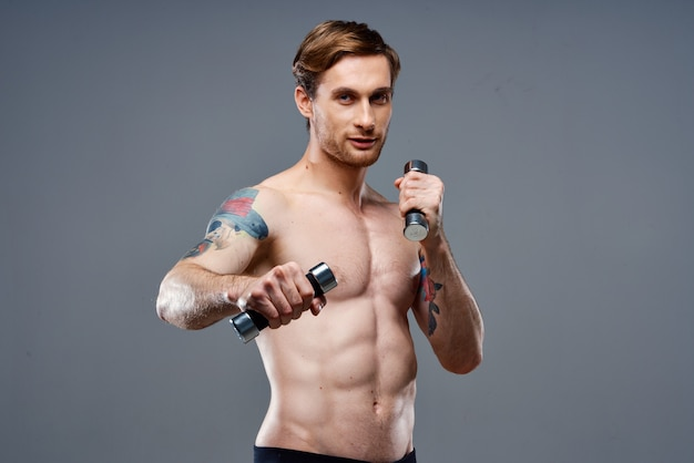 Atleta nudo con un tatuaggio e manubri in bodybuilding fitness telefono mani
