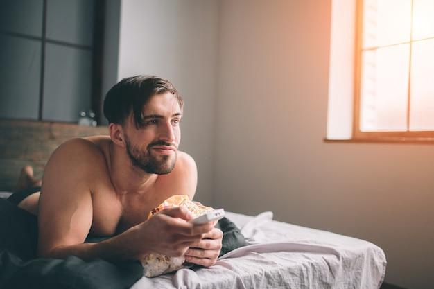 Nudo barbuto con i capelli scuri che guarda la televisione sdraiato sul letto