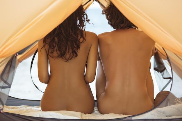 Coppia nuda seduta sulla spiaggia vista posteriore di un bell'uomo nudista e di una bella donna che riposa