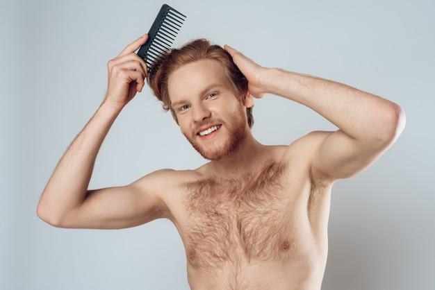 Uomo bello nudo che si pettina