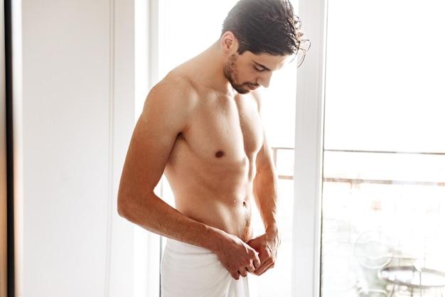 Uomo nudo in piedi al chiuso in bagno con un asciugamano