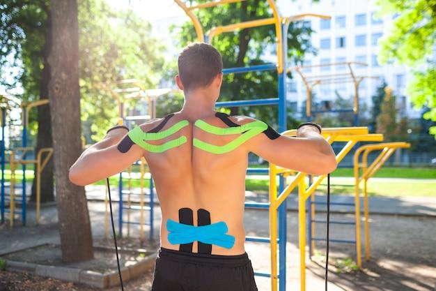Uomo muscoloso nudo allenamento con corda fitness al campo sportivo