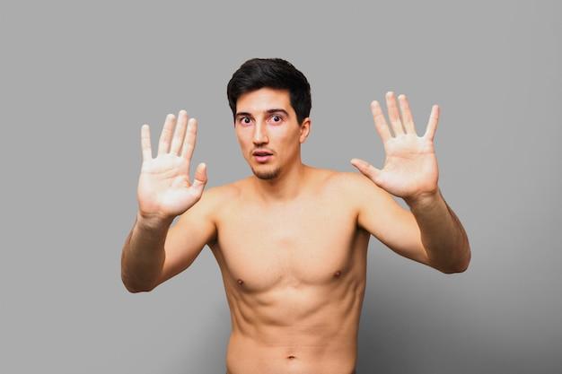 Uomo nudo spaventato del brunette con le mani aperte nella parte anteriore che dice che non è colpevole o che chiede la pietà contro una priorità bassa grigia