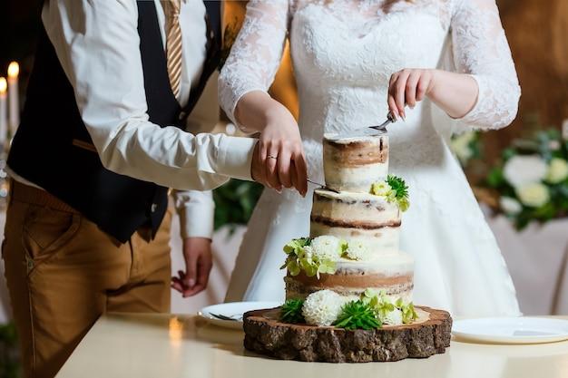Torta nuziale nuda decorata con fiori freschi nel verde delizioso dessert al banchetto di nozze