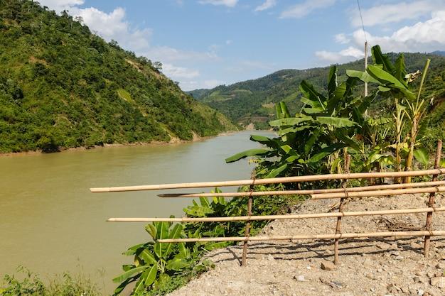 Fiume nam na, fiume di montagna del vietnam e recinzione di bambù in primo piano
