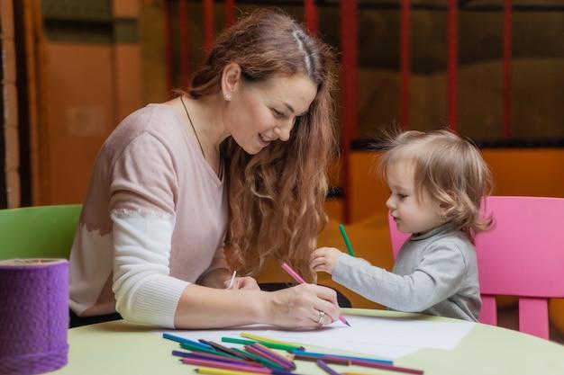 La tata insegna a una bambina come disegnare con le matite colorate mentre è seduta a un tavolo in un centro di intrattenimento per bambini