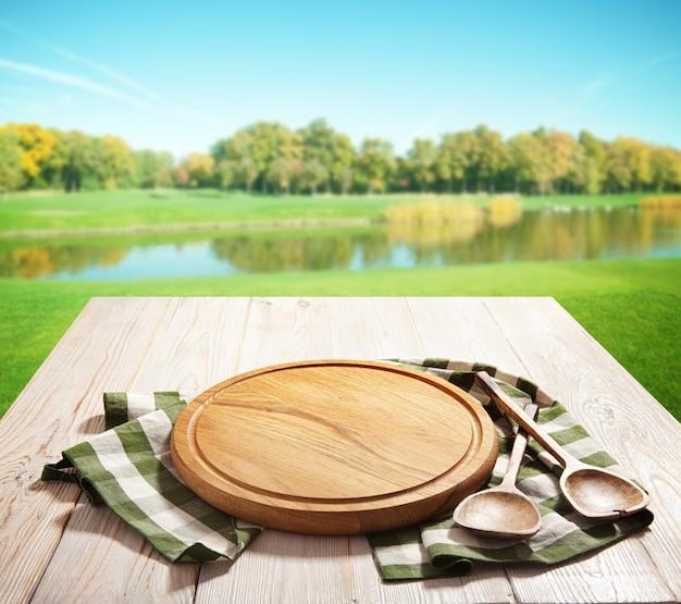 Tovagliolo e tavola per pizza sulla prospettiva del modello di scrivania in legno. fuoco selettivo del fondo di autunno.