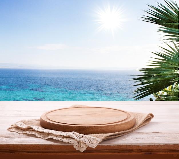 Tovagliolo e tagliere per pizza su scrivania in legno. paesaggio estivo.