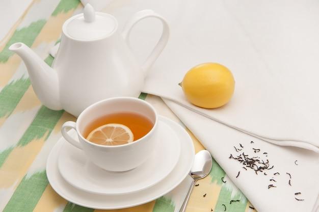 Su un tovagliolo tazza di tè con limone in un piattino e teiera