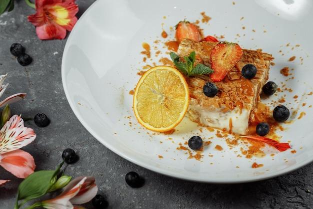 Torta napoleone con salsa al caramello. delicata pasta sfoglia con crema pasticcera e salsa al caramello decorata con fragole, mirtilli e menta